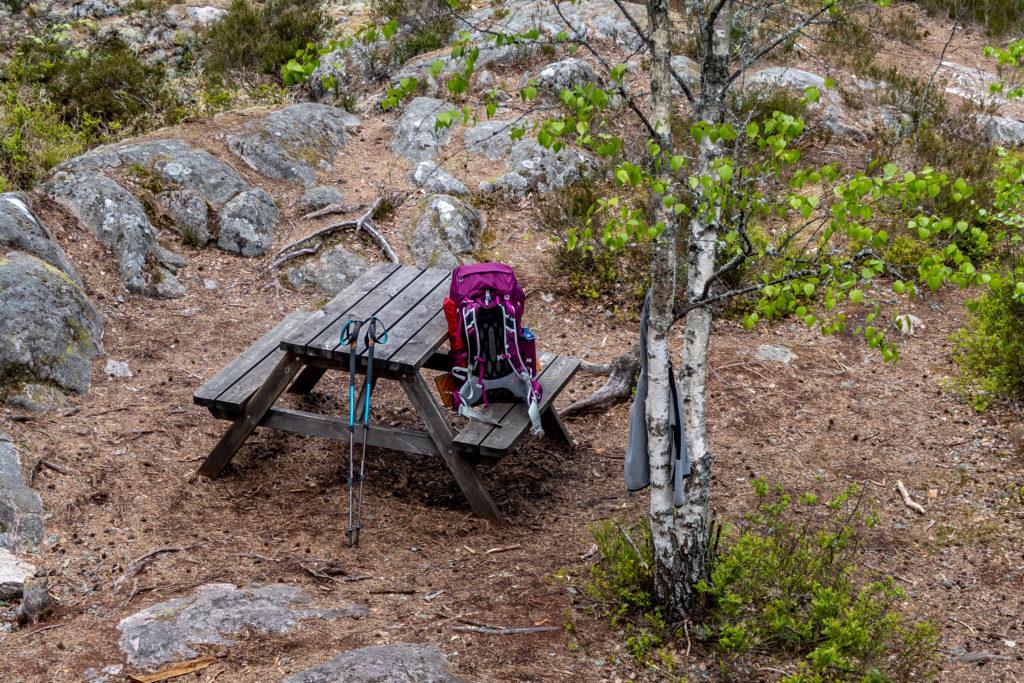 Ryggsäck och vandringsstav vid bord i skogen